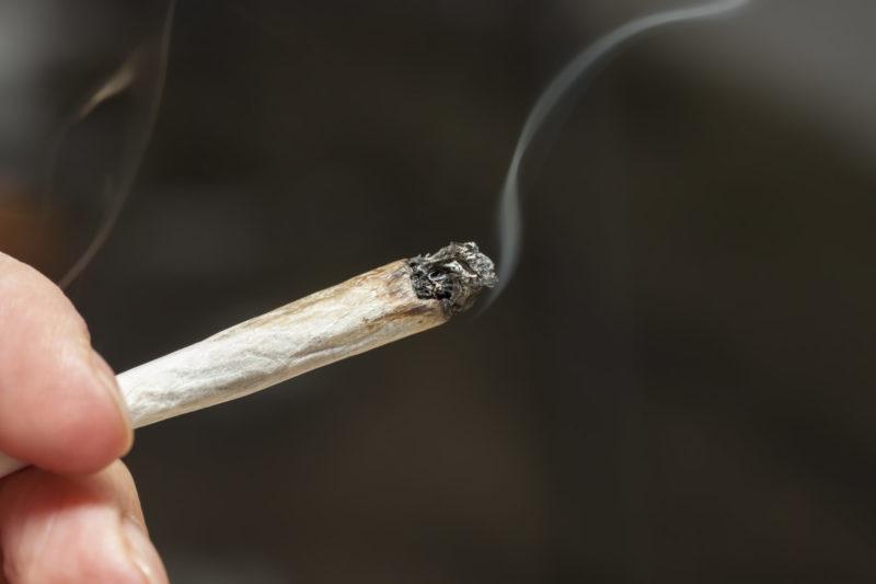 Hand Holding A Lit, Smoking Marijuana Cigarette